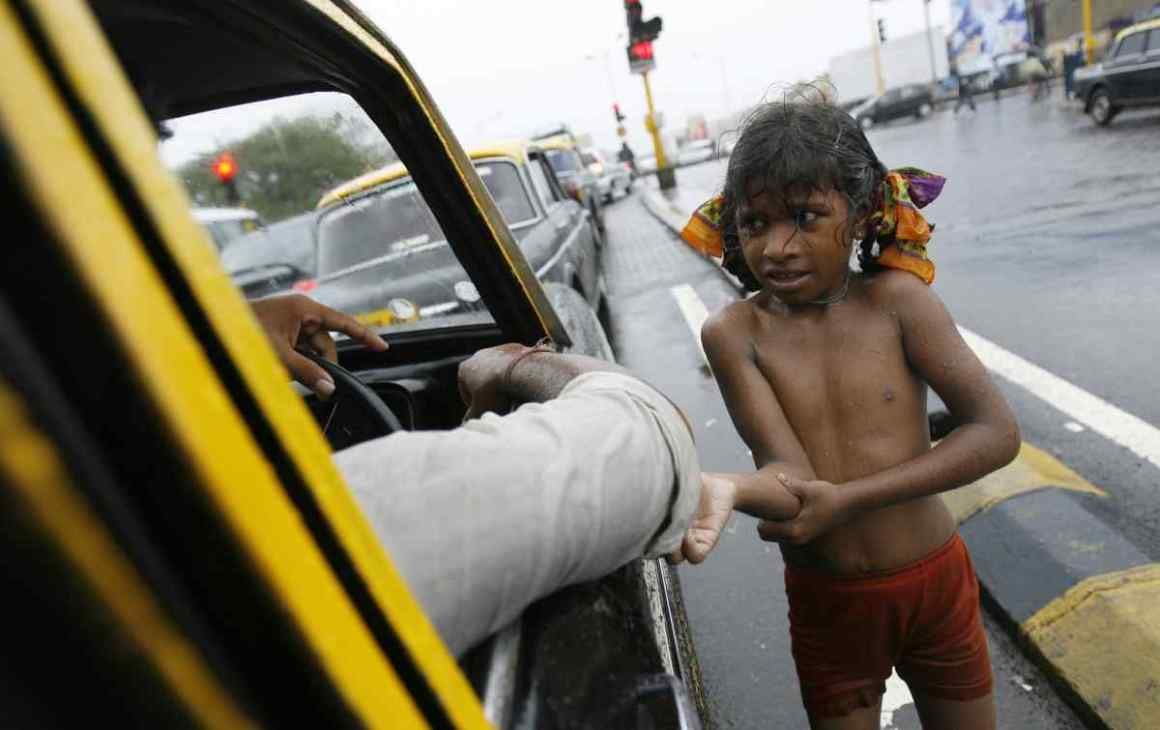A girl begs for alms in rain at a street in Mumbai. (Photo: Reuters)