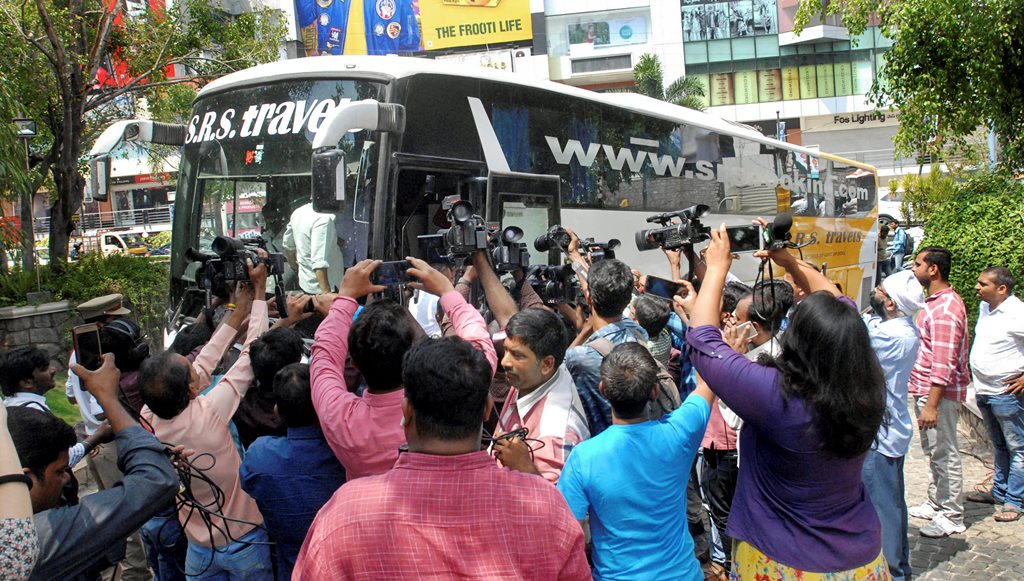 Hyderabad: Media surrounds the bus as Karnataka Congress and JD(S) MLAs arrive at Taj Krishna Hotel, in Hyderabad, on Friday. (PTI Photo) (PTI5_18_2018_000183B)
