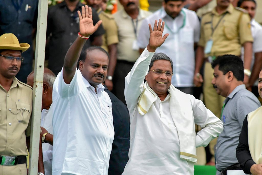 Bengaluru: Newly sworn-in Karnataka Chief Minister H D Kumaraswamy with Karnataka former chief minister & Congress leader Siddaramaiah during the swearing-in ceremony of JD(S)-Congress coalition government, in Bengaluru, on Wednesday. (PTI Photo)(PTI5_23_2018_000160B)