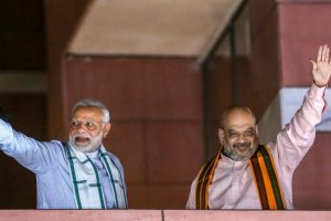New Delhi: Prime Minister Narendra Modi and BJP President Amit Shah wave to party workers gathered at the party headquarters, after the Karnataka Assembly elections result 2018, in New Delhi, on Tuesday. (PTI Photo) (PTI5_15_2018_000229B)