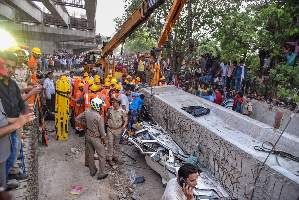 Varanasi: Locals and rescue teams gather near crushed vehicles after a portion of an under-construction flyover collapsed, leaving at least 12 dead, in Varanasi on Tuesday. (PTI Photo) (PTI5_15_2018_000164B)