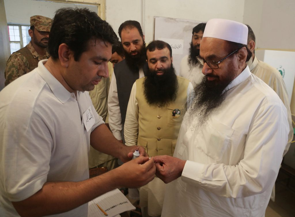 Lahore: An election officer marks a thumb of Hafiz Saeed, right, head of the Pakistani religious party Jamaat-ud-Dawa, at polling station in Lahore, Pakistan, Wednesday, July 25, 2018. After an acrimonious campaign, polls opened in Pakistan on Wednesday to elect the country's third straight civilian government. AP/PTI(AP7_25_2018_000071B)