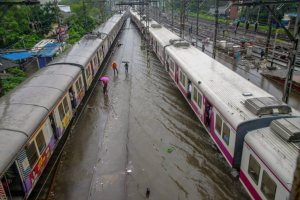 Thane: Suburban trains chug on water-logged tracks during heavy rainfall, in Mumbai on Monday, July 09, 2018. (PTI Photo) (PTI7_9_2018_000178B)