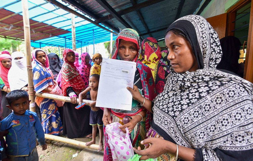 Nagaon: People wait to check their names on the final draft of the state's National Register of Citizens after it was released, at an NRC Seva Kendra in Nagaon on Monday, July 30, 2018. (PTI Photo) (PTI7_30_2018_000127B)
