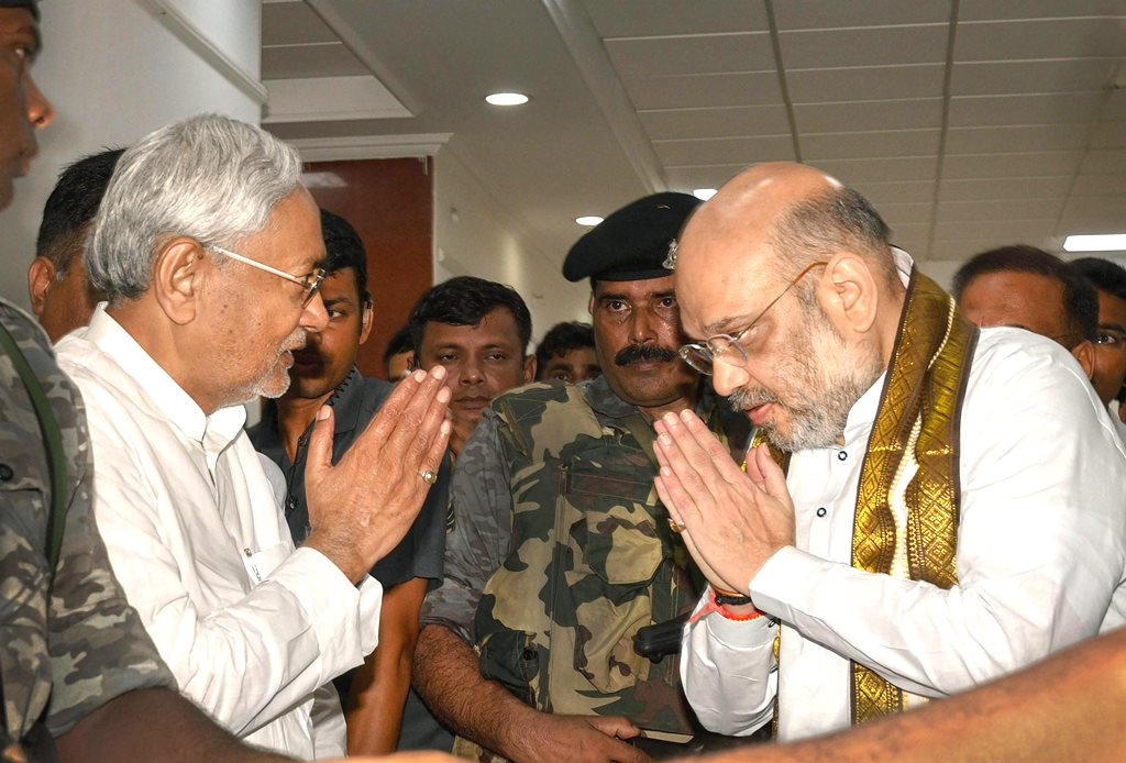 Patna: Bihar Chief Minister Nitish Kumar and Bharatiya Janata Party (BJP) President Amit Shah exchange greetings before a breakfast meeting at the state guest house, in Patna on Thursday, July 12, 2018. (PTI Photo) (PTI7_12_2018_000060B)