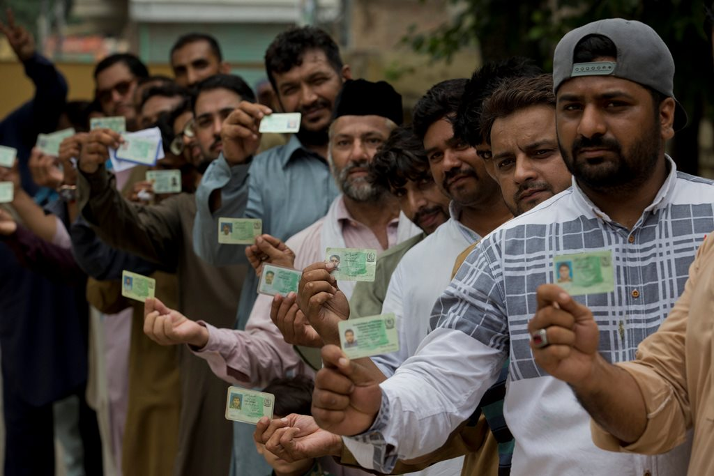 Rawalpindi: Pakistani voters pose with their national identity cards waiting in a queue to cast their votes in Rawalpindi, Pakistan, Wednesday, July 25, 2018. After an acrimonious campaign, polls opened in Pakistan on Wednesday to elect the country's third straight civilian election, a first for this majority Muslim nation that has been directly or indirectly ruled by its military for most of its 71-year history. AP/PTI(AP7_25_2018_000057B)