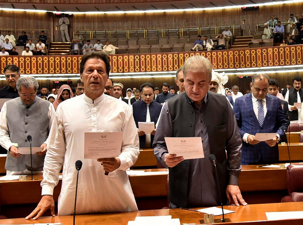 Islamabad : In this photo released by the National Assembly, newly elected parliamentarian Imran Khan, left, takes the oath of office with Shah Mehmood Qureshi, in Islamabad, Pakistan, Monday, Aug. 13, 2018. Pakistan's newly elected parliament convened Monday for the first time since last month's general elections that saw the party of former cricket star turned politician Khan win most seats, propelling him toward the post of the country's next prime minister.AP/PTI(AP8_13_2018_000172B)