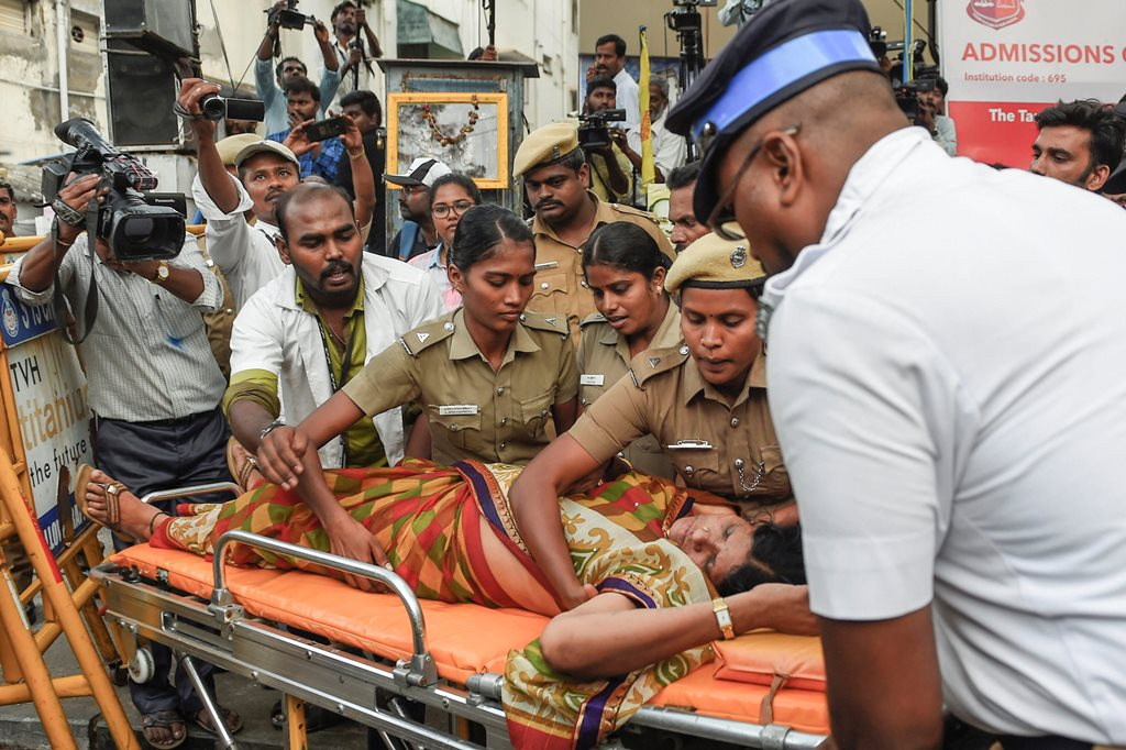 Chennai: A Dravida Munnetra Kazhagam (DMK) supporter being taken for treatment after she fainted outside the hospital, where DMK chief M Karunanidhi is being treated, in Chennai on Monday, July 30, 2018. (PTI Photo) (PTI7_30_2018_000218B)