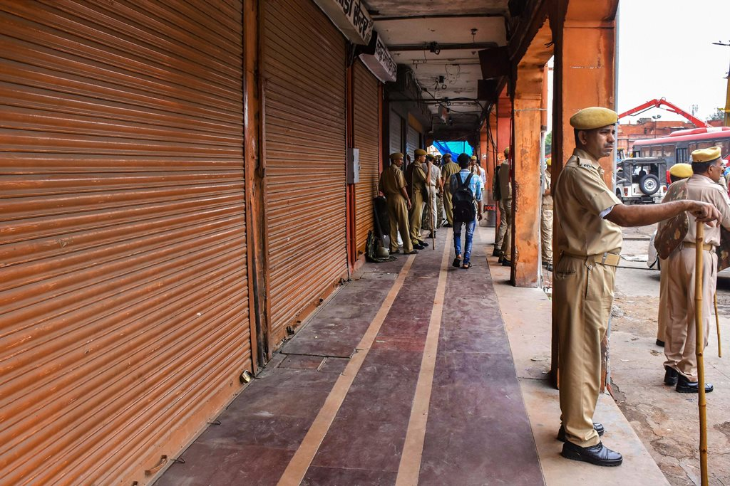 Jaipur: Police personnel guard outside closed shops during the Bharat Bandh, called by the upper-caste organisations in protest over the recent amendment of the SC/ST Act, in Jaipur, Thursday, Sept 6, 2018. (PTI Photo) (PTI9_6_2018_000095B)