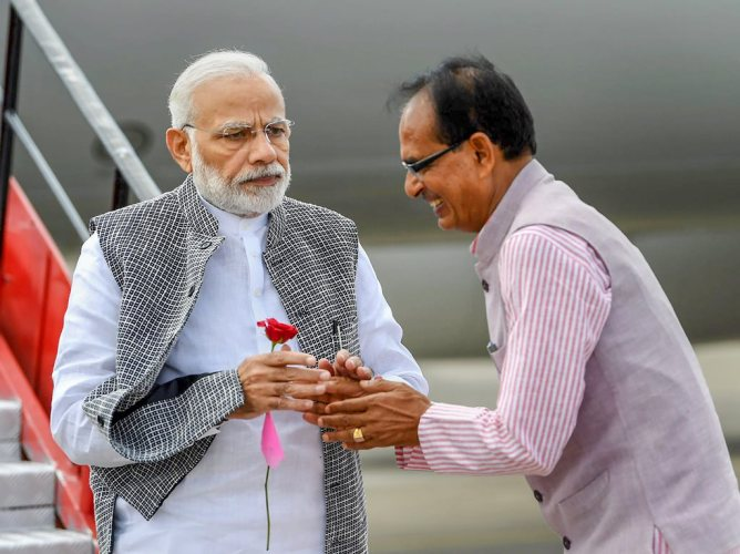 Indore: Prime Minister Narendra Modi being received by the Chief Minister of Madhya Pradesh Shivraj Singh Chouhan on his arrival in Indore, Friday, Sep 14, 2018. PM Modi arrived in the city to attend Ashara Mubaraka, commemoration of the martyrdom of Imam Husain (SA), organised by the Dawoodi Bohra community. (PIB Photo via PTI) (PTI9_14_2018_000057B)