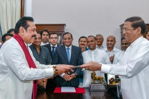 Sri Lanka's former President Mahinda Rajapaksa (Front-L) is sworn in as the new Prime Minister before President Maithripala Sirisena in Colombo, Sri Lanka October 26, 2018. Sri Lanka's President's Office/Handout via REUTERS
