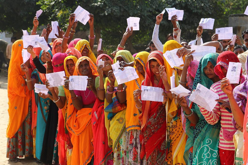 EDS PLS TAKE NOTE OF THIS PTI PICK OF THE DAY:::::::: Jaipur: Voters show their identity cards as they queue to cast their vote for the state Assembly elections, outside a polling station at Samred village of Jaipur district, Friday, Dec. 07, 2018. (PTI Photo)(PTI12_7_2018_000159B)(PTI12_7_2018_000187B)