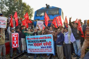 "Guwahati: Centre of Indian Trade Union (CITU) activists and ally organizations block a train during the 48-hour-long nationwide general strike called by central trade unions protesting against the ""anti-people"" policies of the Centre, in Guwahati, Tuesday, Jan 8, 2019. (PTI Photo)  (PTI1_8_2019_000044B)"