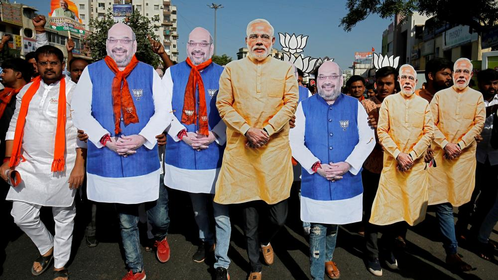 BJP supporters wearing cut-outs of Prime Minister Narendra Modi and the party president Amit Shah at a campaign event in Ahmedabad, April 2019. Photo AMIT DAVE/REUTERS
