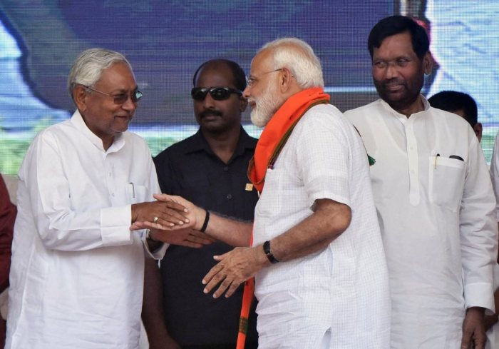 Forbesganj: Prime Minister Narendra Modi shakes hands with Bihar Chief Minister and Janta Dal United President Nitish Kumar as Lok Janshakti Party (LJP) chief Ram Vilas Paswan looks on, during an election rally at Araria lok sabha constituency, in Forbesganj, Saturday, April 20, 2019. (PTI Photo) (PTI4_20_2019_000017B)