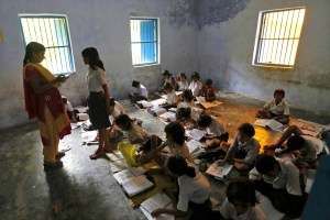 Schoolchildren study inside their classroom after having their free mid-day meal, distributed by a government-run primary school, at Brahimpur village in Chapra district of the eastern Indian state of Bihar July 19, 2013. The midday meal scheme of giving school pupils a free lunch is the largest such programme in the world. It has been widely lauded as one of the most successful welfare measures in India, home to a quarter of the world's hungry, because it also boosts school enrolments and helps children to continue studies. For millions of poor families, the lunch is the only full meal their children eat in a day. That encourages them to send them to school, and not keep them home to help with chores. For this reason, despite being poorly managed, the scheme draws a lot of support from non-governmental organisations, rights activists and the United Nations. Picture taken July 19, 2013. REUTERS/Adnan Abidi (INDIA - Tags: HEALTH FOOD EDUCATION SOCIETY) - RTX11TH7