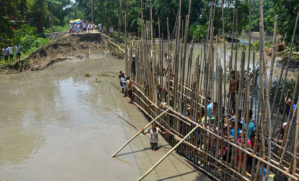 Hajo: Local people construct an embankment with bamboo and sand bags which was breached by the swollen Brahmaputra River, at Monakuchi village in Hajo district of Assam, Thursday, July 18, 2019. (PTI Photo) (PTI7_18_2019_000151B)