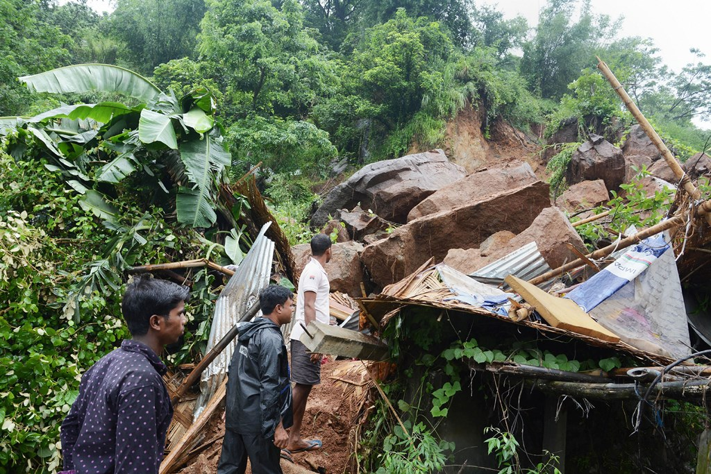 Guwahati: People look on at the site of a landslide, caused by continuous monsoon rain in Guwahati, Wednesday, July 10, 2019. The incident lead to the death of 47-year-old Narayan Saha. (PTI Photo) (PTI7_10_2019_000091B)