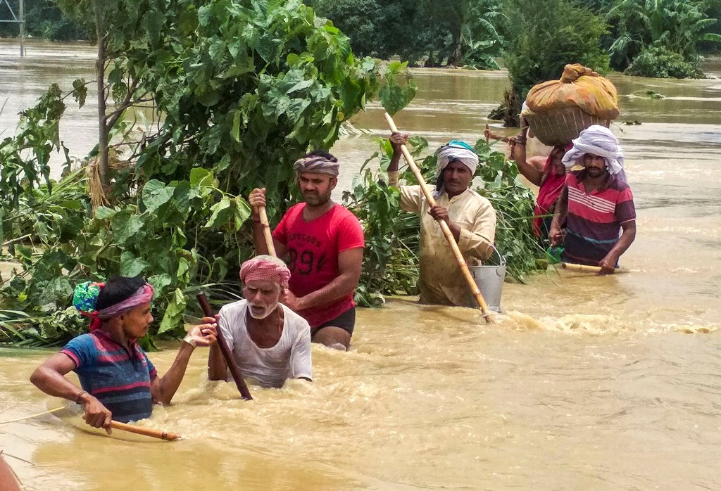 Madhubani: People cross a flooded street following incessant monsoon rainfall, at Madhubani district, Monday, July 15, 2019. The death toll in the Bihar floods mounted to 24, with 2.6 million people reeling from the deluge in 12 districts of the state. (PTI Photo) (PTI7_16_2019_000131B)