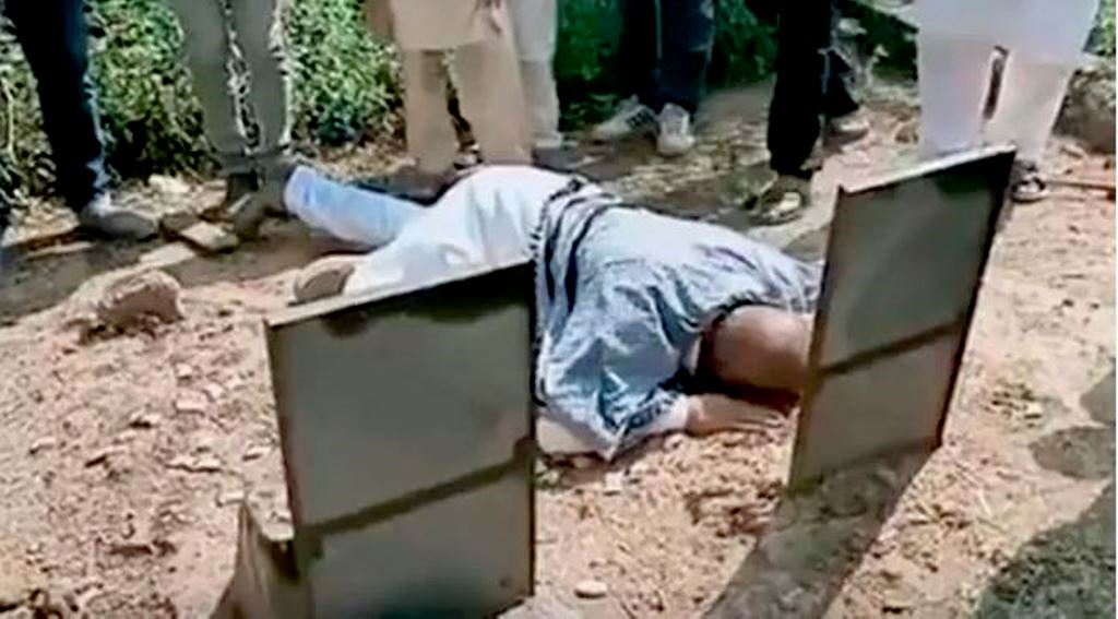 आतंक के आरोप से बरी होने के 23 साल बाद श्रीनगर में अपने पिता की कब्र के पास मोहम्मद अली भट. (फोटो साभार: वीडियो ग्रैब)
