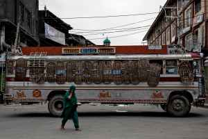 A Kashmiri woman walks past a bus used as a road block by Indian security personnel during restrictions after the scrapping of the special constitutional status for Kashmir by the government, in Srinagar, August 11, 2019. REUTERS/Danish Siddiqui