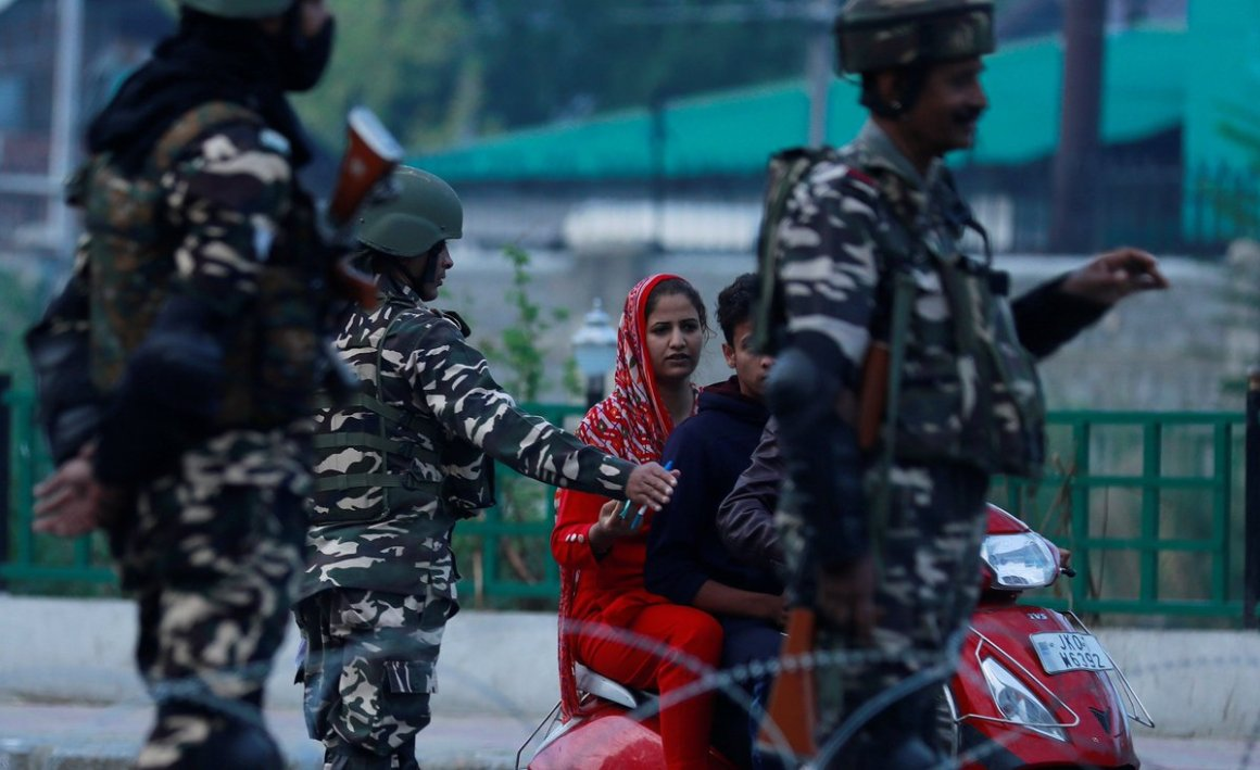 Indian security personnel stop Kashmiri residents as they stand guard on a deserted road during restrictions after scrapping of the special constitutional status for Kashmir by the Indian government, in Srinagar, August 23, 2019. REUTERS/Danish Ismail