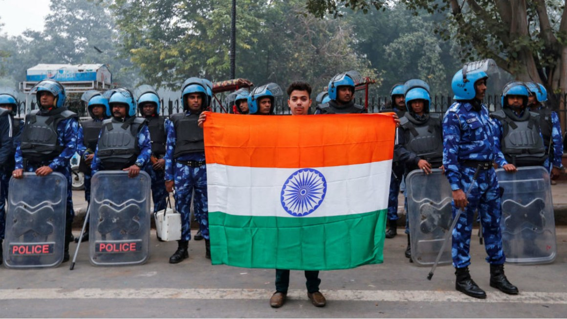 Mohammad Anas Qureshi, 20, who is a fruit vendor, poses for photo with the national flag of India in front of riot police during a protest against a new citizenship law in Delhi, India, December 19, 2019. Danish Siddiqui, Reuters