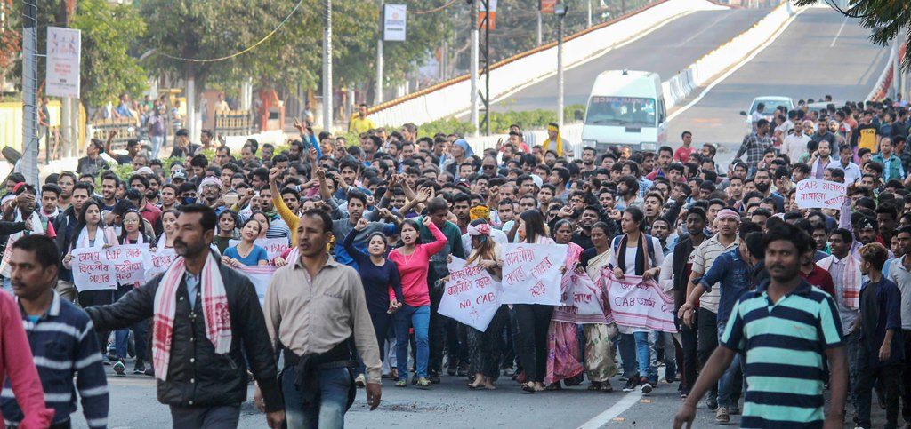 Guwahati: Protestors raise slogans as they take part in a demonstration against the passing of Citizenship (Amendment) Bill during curfew, at GS Road in Guwahati, Thursday, Dec. 12, 2019. Thousands of people defied curfew in Guwahati and took to the streets, prompting police to open fire, even as protests against the contentious Citizenship (Amendment) Bill intensified in the state. (PTI Photo)(PTI12_12_2019_000196B)