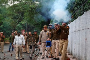New Delhi: A police personnel fires tear gas as students of Jamia Millia Islamia University stage a protest against the passing of Citizenship Amendment Bill, in New Delhi, Friday, Dec. 13, 2019. (PTI Photo) (PTI12_13_2019_000384B)