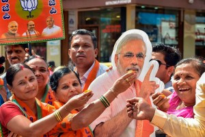 Hubballi: BJP supporters offer sweets to a cut-out of Prime Minister Narendra Modi after the party won in 12 out of 15 assembly constituencies of Karnataka securing the position of Yediyurappa-led BJP government in the state, in Hubballi, Monday, Dec. 9, 2019. (PTI Photo) (PTI12_9_2019_000091B)