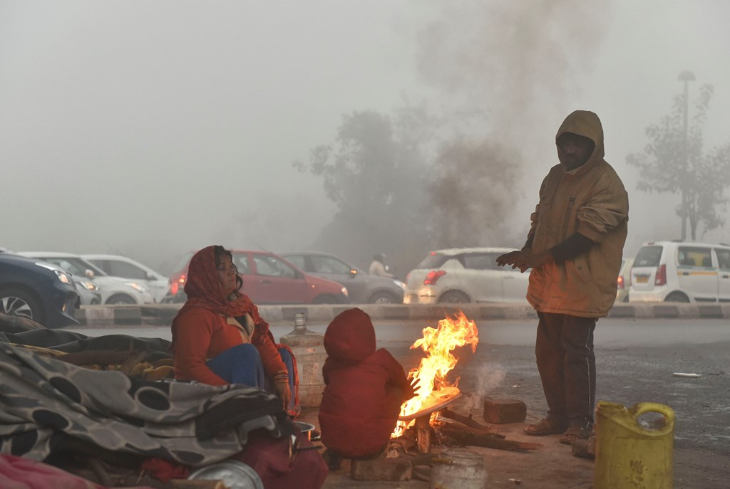 New Delhi: People warm themselves near a bonfire during a cold and foggy morning in New Delhi, Monday, Dec 30,2019. A thick blanket of fog engulfed the national capital on Monday morning affecting train and flight operations as visibility dropped drastically, with some observatories recording it at zero metres. (PTI Photo/Kamal Kishore) (PTI12_30_2019_000040B)