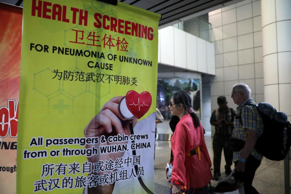 Passengers pass a banner about the Wuhan coronavirus at a thermal screening point in the international arrival terminal of Kuala Lumpur International Airport in Malaysia on Tuesday. Photo: Reuters