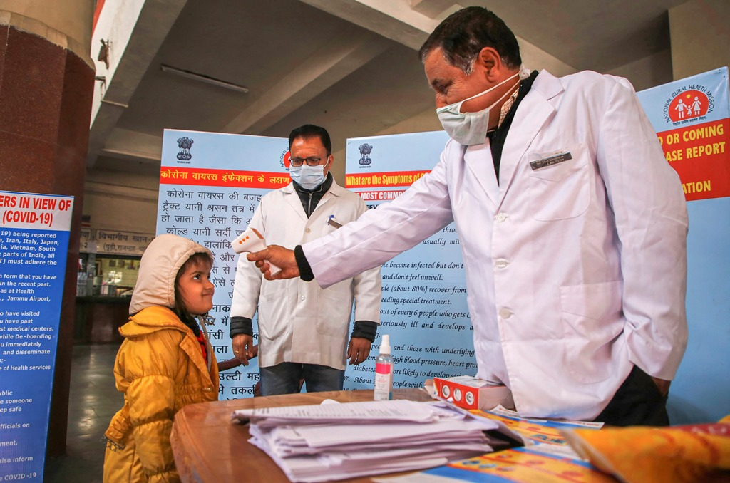Jammu: A doctor checks the temperature of a child passenger as part of precautionary measures against the new coronavirus, at a railway station in Jammu, Thursday, March 12, 2020. (PTI Photo) (PTI12-03-2020_000050B)
