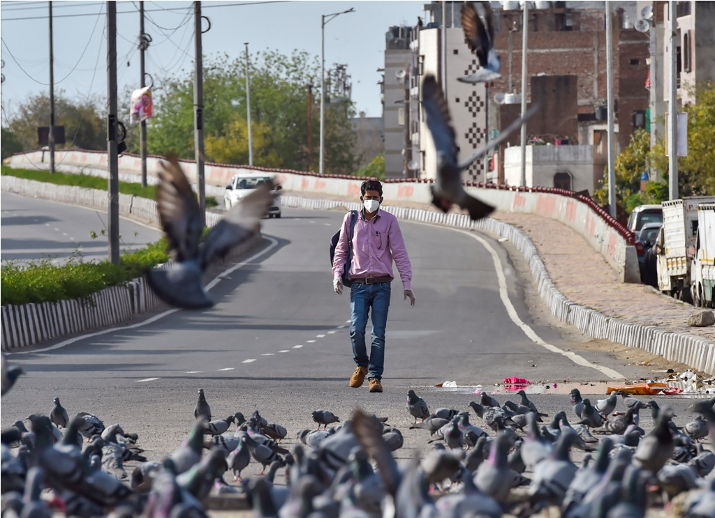 New Delhi: A man wearing face mask walks on a road during the complete lockdown imposed to contain the spread of novel coronavirus, in New Delhi, Wednesday, March 25, 2020. (PTI Photo/Ravi Choudhary)(PTI25-03-2020_000242B)