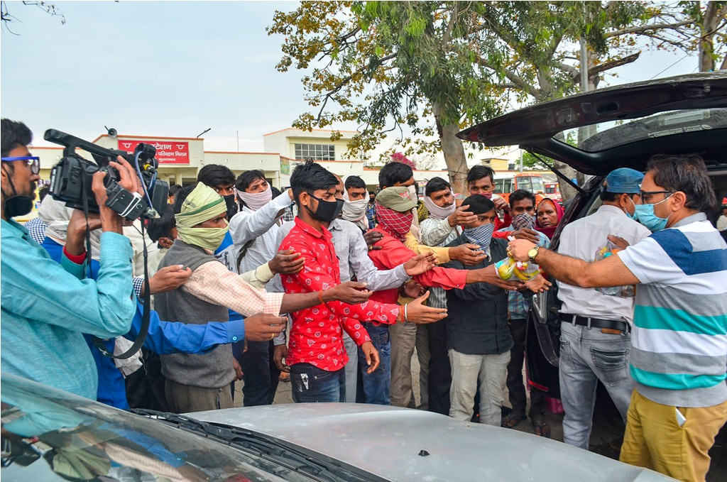 Moradabad: Volunteers serve food to homeless people and migrant daily wagers waiting at a bus stop for transportation to return to their native places, during the nationwide lockdown imposed in the wake of coronavirus pandemic, in Moradabad, Friday, March 27, 2020. (PTI Photo)