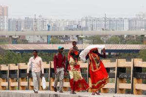 A migrant worker carries her daughter as she walks on a highway with others looking out for a transport to return to their villages, after India ordered a 21-day nationwide lockdown to limit the spreading of coronavirus disease (COVID-19), in Ghaziabad, on the outskirts of New Delhi, March 26, 2020. REUTERS/Adnan Abidi