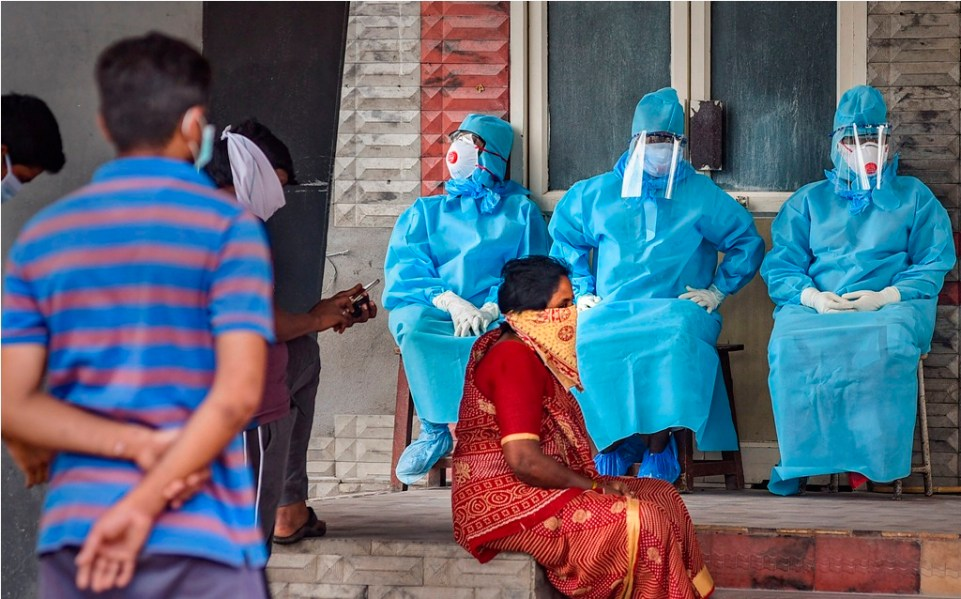 Vijayawada: Workers wearing protective suits sit outside an isolation ward at Government General Hospital during the nationwide lockdown, imposed in wake of the coronavirus pandemic, in Vijayawada, Monday, April 20, 2020. (PTI Photo)(PTI20-04-2020_000165B)