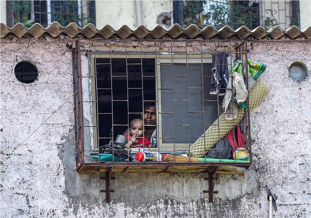 Mumbai: A man along with his child looks through the window of his house during a nationwide lockdown in the wake of coronavirus pandemic, at Dharavi in Mumbai, Thursday, April 2, 2020. The death of a COVID-19 patient from Mumbais Dharavi, known as one of the biggest slums in Asia, has exposed its residents to the vulnerability of contracting the viral infection and sparked a fear of its spread in the highly congested area. (PTI Photo/Kunal Patil)(PTI02-04-2020 000142B)