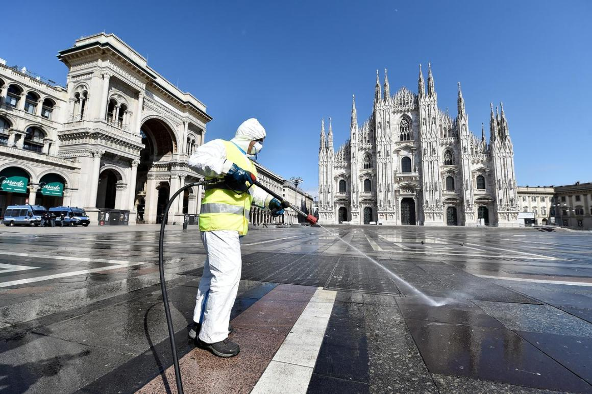 FILE PHOTO: A worker wearing protective garments sanitises the Duomo square, during the coronavirus disease (COVID-19) outbreak in central Milan, Italy March 31, 2020. REUTERS/Flavio Lo Scalzo