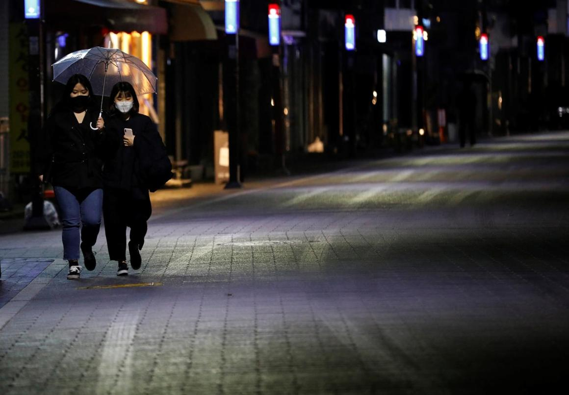 Women wearing masks make their way in downtown amid the rise in confirmed cases of the coronavirus disease (COVID-19) in Daegu, South Korea, March 9, 2020. REUTERS/Kim Kyung-Hoon