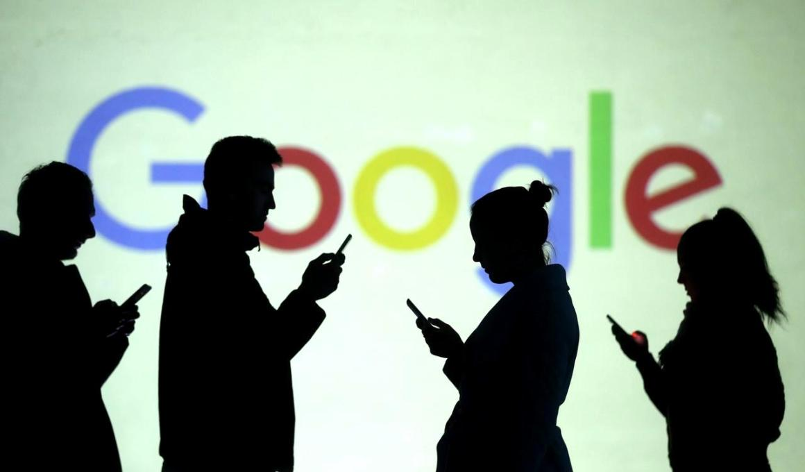 Silhouettes of mobile users are seen next to a screen projection of Google logo in this picture illustration taken March 28, 2018. REUTERS/Dado Ruvic