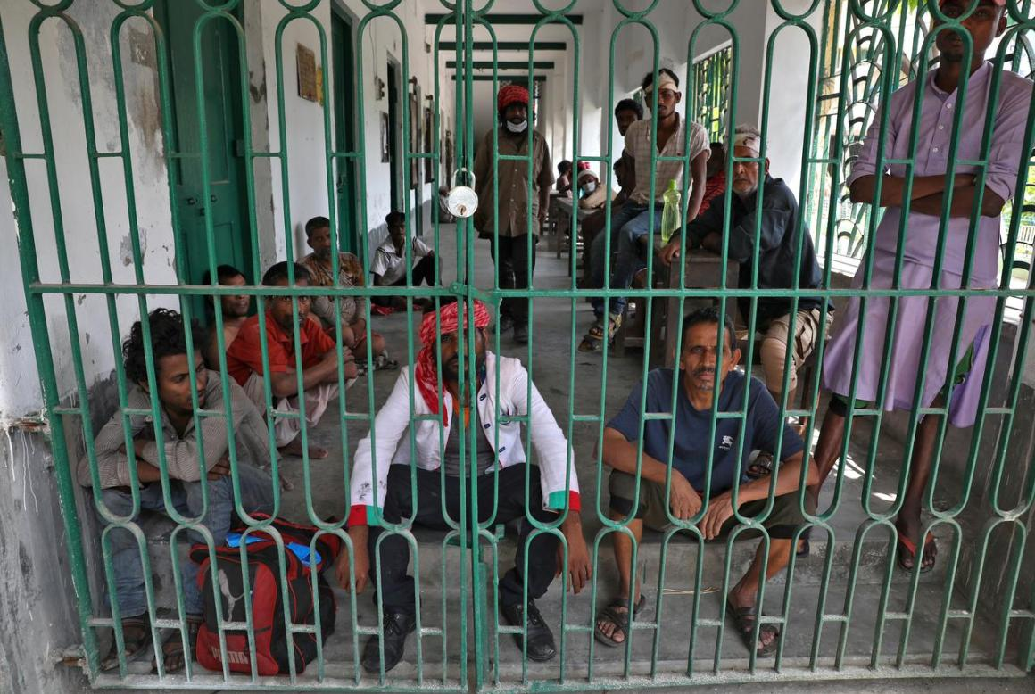 Homeless people sit inside a corridor of a locked shelter during a 21-day nationwide lockdown to slow the spreading of the coronavirus disease (COVID-19) at Howrah, on the outskirts of Kolkata, India, April 3, 2020. REUTERS/Rupak De Chowdhuri