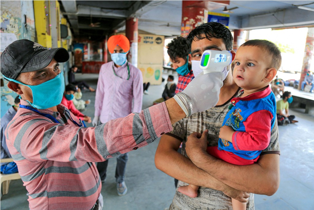Bathinda:A healthcare worker checks the temperature of child as people arrive to board a bus arranged by the Punjab government to help them reach their native places during the nationwide lockdown, imposed to stop the spread of the coronavirus, in Bathinda, Friday, May 1, 2020. (PTI Photo)(PTI01-05-2020_000214B)