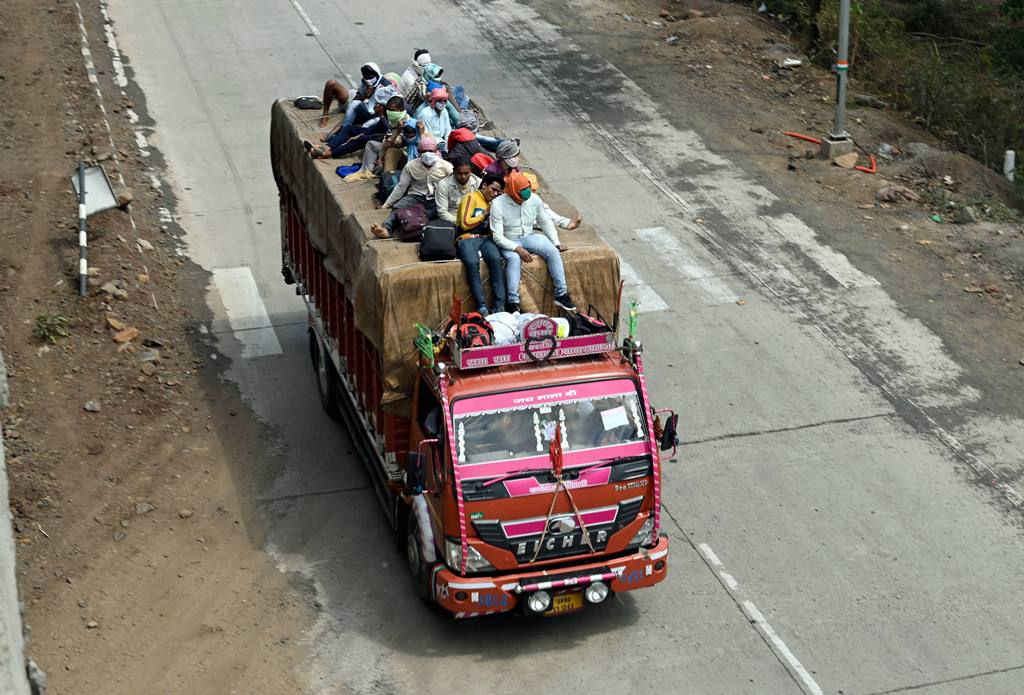 Jabalpur: Migrants travel atop a loaded truck to their native places, during the ongoing COVID-19 nationwide lockdown, in Jabalpur, Wednesday, May 13, 2020. (PTI Photo)(PTI13-05-2020 000073B)