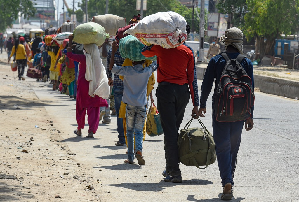 Dadri: Migrant workers wait in a queue while being lodged at a camp by the Uttar Pradesh government, during ongoing COVID-19 lockdown, at Dadri in Gautam Buddha Nagar district, Wednesday, May 20, 2020. (PTI Photo/Atul Yadav) (PTI20-05-2020 000206B)
