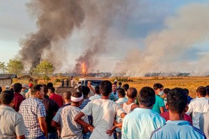 Tinsukia: Locals look on as smoke billows from a fire at Baghjan oil field, a week after a blowout, in Tinsukia district, Tuesday, June 9, 2020. A team from Singapore was called to assess the reason of the blowout yesterday. (PTI Photo)(PTI09-06-2020_000160B)