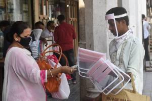 Kolkata: A woman buys face shield from a hawker during the fifth phase of COVID-19 lockdown, in Kolkata, Friday, June 5, 2020. (PTI Photo/Ashok Bhaumik)(PTI05-06-2020 000126B)