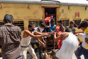 Allahabad: A group of migrants engage in a scuffle for packets of free food and water bottles distributed by railway officials during ongoing COVID-19 lockdown, at the railway station in Allahabad, Monday, June 1, 2020. (PTI Photo)(PTI01-06-2020 000217B)(PTI01-06-2020 000317B)