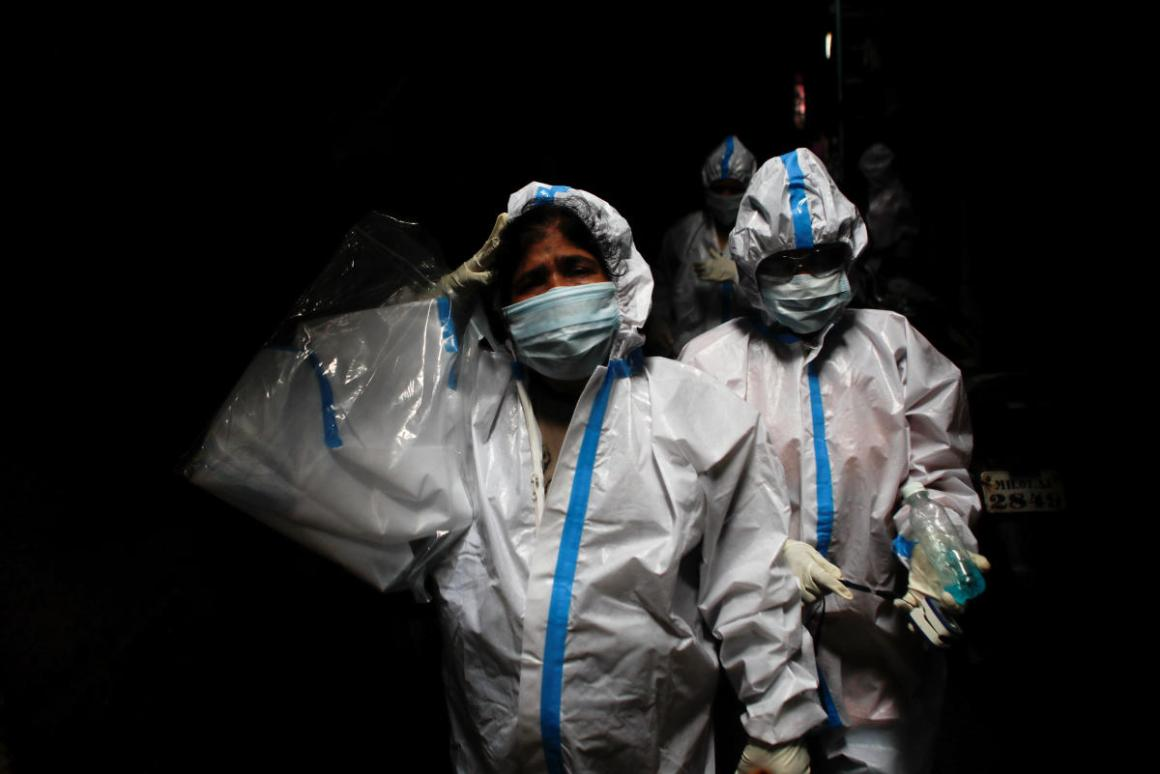 A health worker in personal protective equipment reacts as she and the rest of the team walk through an alley during a check up campaign for the coronavirus disease (COVID-19) at a slum area in Mumbai. Credit: Reuters.