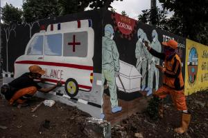 FILE PHOTO: Workers paint a mural promoting coronavirus disease (COVID-19) awareness in Jakarta, Indonesia August 11, 2020, in this photo taken by Antara Foto/Aprillio Akbar/via Reuters